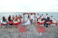 Red beach wedding decorations on Assateague Isand - Wedding Minister Sean Rox - archway by Rox Beach Weddings of Ocean City, MD:  https://www.roxbeachweddings.com/