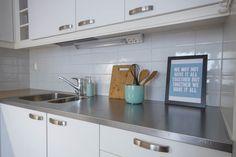 Turkoosit yksityiskohdat piristävät vaaleaa keittiötä. Vaihtokehyksiin voi vaihtaa sopivan värisen kuvan muiden yksityiskohtien mukaan.