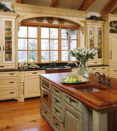 Cream cabinets, light blue island and wood counter tops.