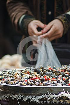 Hands of a shopper and a basket of chili peppered freshwater clams, as seen in an outdoor market in Cambodia, Southeast Asia.