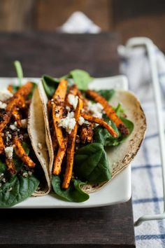 A spicy sweet potato taco spiced with a mole seasoning and topped with spinach and some crispy quinoa.