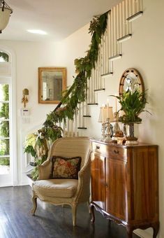 A sunny entryway with simple seasonal d�cor. Artichokes and a silver bow are fun trimming on a garland of greenery.