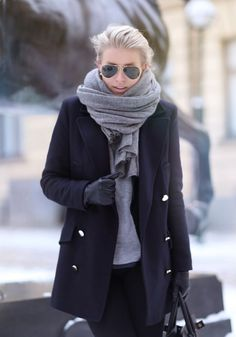 This combo of a black coat and black skinny jeans will attract attention for all the right reasons. Shop this look for $59: lookastic.com/... — Black Sunglasses — Grey Scarf — Grey Long Sleeve T-shirt — Black Leather Gloves — Black Coat — Black Skinny Jeans