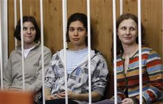 Members of female punk band 'Pussy Riot', Nadezhda Tolokonnikova (C), Maria Alyokhina (R) and Yekaterina Samutsevich, sit behind bars before a court hearing in Moscow, July 20, 2012. They are on trial for a protest performance against Vladmir Putin.
