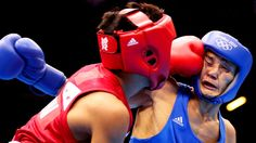 Birzhan Zhakypov of Kazakhstan (right) takes a blow from Mark Barriga of the Philippines during the men's light fly (46-49kg) boxing on Day 8 of the London 2012 Olympic Games.