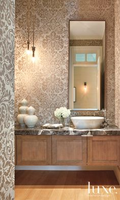The powder room in this Brentwood home features an onyx countertop and a printed grass-cloth wallcovering.