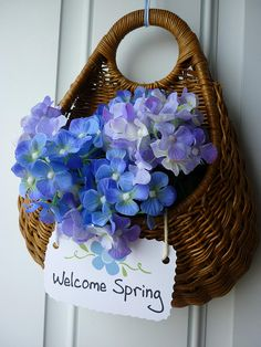 "Wicker Basket filled with flowers and a tag ""Welcome Spring"""