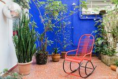 Quintal com parede pintada de azul, chuveirão, cadeira espaguete e piso antigo de caquinhos