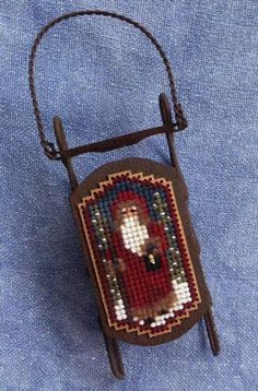 Foxwood Crossings Cross-Stitch Designs brings us another sled ornament with the Tiny Twilight Santa.