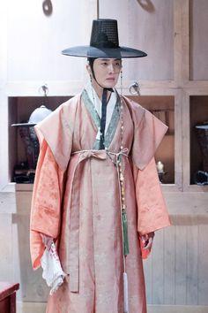"""Jung Ilwoo ในชุดฮันบก สวมใส่เสื้อคลุมยาวสีส้ม """"도포-Dopo (โดโพ่)"""" และสวมทับด้วย """"답호- Dapho (ดับโฮ)"""" (เสื้อยาวแขนสั้น มีปกคอเสื้อซ้อนกัน และมี """"옷고름 –โอซโกรึม"""" ไว้ผูกติดกันบริเวณหน้าอก) -SEON INJOO-"""