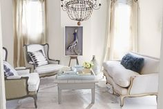 In this Atlanta loft's living room, Aidan Gray wingback chairs, upholstered in cotton and burlap, complement a sofa the homeowner found at a Paris flea market. She fashioned the coffee table (painted in Gothic Arch by Benjamin Moore) by cutting a farm table down to size, then painting it warm gray. A wooden stool from a Toronto thrift shop elevates a shadow-boxed heron. The Mongolian-lambhair pillow is by West Elm, the tie-dyed cushions by Kevin O'Brien.   - CountryLiving.com