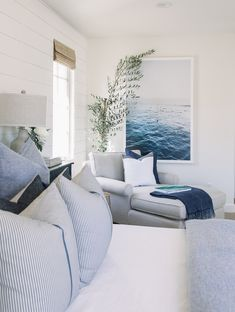 A large piece of ocean art defines the lounging area in the bedroom of this beach bungalow. Featured on Completely Coastal along with other rooms that have the ocean as a focal point.