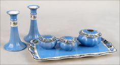 VICTORIAN GLAZED CERAMIC VANITY SET.  Comprised of a tray, three vanity jars, and a pair of candlesticks. All pieces have transferred floral bordering Candlestick height: 6.5