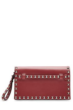 Valentino's+lipstick+red+clutch+is+detailed+with+the+brand's+signature+gold-tone+stud+embellishment.+Linear+and+luxe,+it+will+add+status+and+statement+to+any+look+#Stylebop