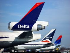 """Delta Air Lines McDonnell Douglas MD-11 N811DE wearing the """"Interim"""" livery at Atlanta-Hartsfield, January 2002. Alongside are a company Boeing 757-232 N643DL showcasing the """"Classic Widget"""" and a company Boeing 737-832 N3760C in the """"Flying Colors"""" scheme. (Photo: Peachair)"""