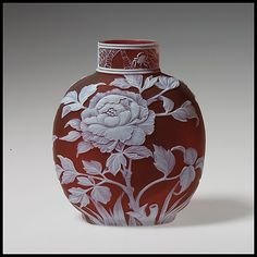 "Peony, late 19th C., The anonymous skilled engraver used acid etching, wheel engraving, and carving with a hand-held blade to achieve a cameo effect upon ""strata"" of clear, crimson, and white glass. The spiderweb on the neck refers to the firm of Thomas Webb, a major reviver of cameo glass. From the Metropolitan Museum Collection"