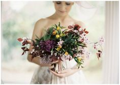 free & wild bouquet with olive branches and kumquats and deep reds and plum with pale blush mixed in