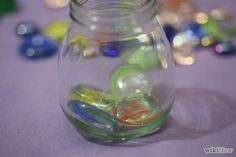 Step 4: Place a thin layer of marbles at the bottom of the jar.