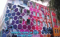 """Alveare coloratissimo su un edificio decrepito: Marina Zumi e il suo murale Ci troviamo in Sassonia (Germania). Qui la nota street artist brasiliana Marina Zumi ha regalato un tocco di allegria ad una costruzione angolare di Halle una delle principali città della regione. L'opera si chiama """"Honeycomb of Life"""" ed è un coloratissimo alveare FONTE  street art murale marina zuma alveare"""