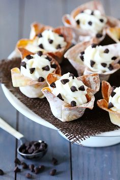 1 package (16 oz.) wonton wrappers  1 container (15 oz.) ricotta cheese  1/4 cup cornstarch  1 1/3 cups whole milk  1/2 cups powdered sugar  1/2 tsp. almond extract  1/2 tsp. vanilla extract  1/4 tsp cinnamon (optional)  2 cups mini semisweet chocolate chips  powdered sugar (for dusting)