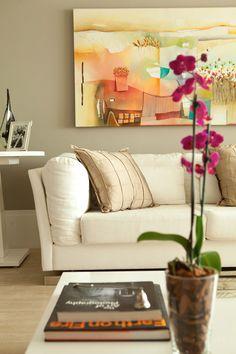 Detalhe de decoração de sala de estar. Living com paredes na cor fendi e sofá branco. Tela colorida dá vida ao ambiente. Projeto de design de interiores e reforma residencial para apartamento em Moema, São Paulo.
