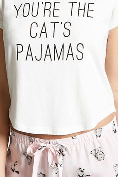 """A PJ set featuring a knit tee with a """"You're The Cat's Pajamas"""" chest graphic, a round neckline, short sleeves, and a curved hem, and a pair of woven shorts with an allover cat print, elasticized drawstring waist, and a ruffled hem."""