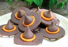 Witch Hat Recipe: 1 bag of Hershey's Kisses, 1 tube of orange icing, 1 pack of the chocolate striped cookies with the hole in the center. Now, turn the cookie upside down, so that the chocolate side faces up. Use the orange icing to make a line around the outside of the center hole. Place the Hershey Kiss over each cookie hole. That's it! Super easy and the kids will love these!