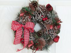 "Such a wonderful way to welcome in the autumn and holiday season! This pinecone 10-inch wreath has 2 tin moose and one tin deer (which are 3 1/2 x 4"") and painted in a warm brown color. It is filled with berries, acorns and flocked in a cinnamon colored snow. A traditional taffeta gingham red checked ribbon gives the warmth of a rustic lodge feeling. Leave hanging year round for those who enjoy having rustic decor."