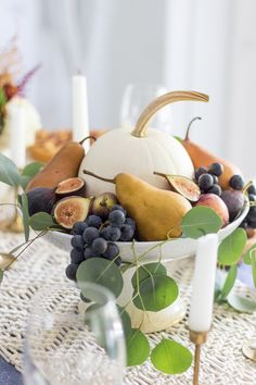 A beautiful tablescape with rich fall colors featuring a centerpiece of fall fruits: Plums, pears, figs, and grapes surround a simple white pumpkin. Fruit Centerpieces, Thanksgiving Centerpieces, Thanksgiving Table, Centerpiece Wedding, Holiday Tables, Holiday Parties, Wedding Decor, Wedding Ideas, Halloween