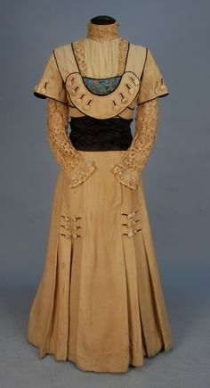 (Photo 1 of 2) Early 20th century heavy silk walking suit. Dress and jacket of natural ottoman lavishly trimmed with black piped scallops, 84 self buttons, blue Chinese figural embroidered silk. High neck dress having handmade bobbin lace under sleeves and bodice trim, black satin cummerbund, two large brass portrait buttons at back waist. Jacket with deep cuff, faux pockets, and Chinese silk faux vest. Via Johnston Estate.