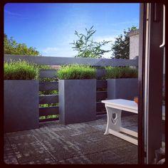 Smalle lange plantenbakken als balkon afscherming.