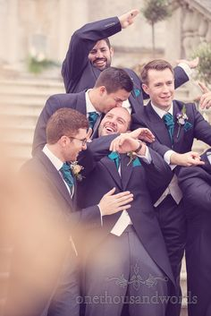Groomsmen mess about with groom during Lulworth Castle wedding group photographs. Photography by one thousand words wedding photographers