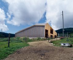 lausanne-based practice LOCALARCHITECTURE has completed a contemporary cow shed in the hills of the jura, switzerland.