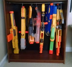Hanging Nerf Storage: bottom of the bookshelf, I used a spring loaded curtain rod and S-Hooks to hang the larger guns. The BIG GUNS!