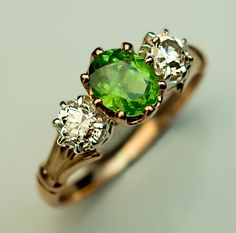 """A Vintage Russian Three-Stone Demantoid and Diamond Ring, 1930s. The 14K gold ring is centered with a sparkling 0.85 ct Russian demantoid with prominent """"horsetails"""", flanked by two old European cut diamonds."""