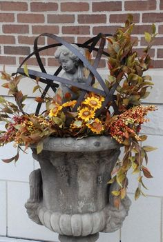 Garden statue angel inside metal orb perched on antique urn with fall foliage porch decor.