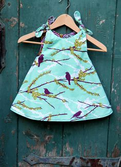 The Girls Aviary Reversible Dress is a comfortable, yet totally chic item for your little ladies wardrobe.    Made from 100% designer cotton fabric, this dress is fully reversible! Its like having two looks in one!! One side of the dress is a gorgeous aqua blue fabric with white and plum colored branches and birds. The interior fabric is a modern plum circle pattern. Dress ties at the shoulder and has a nice loose, swing feeling to it - perfect for your little one who likes to twirl.    This…