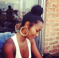 top knot, chunky earrings, and tank. love the effortless simple look