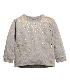 Grau/Glitzer. Sweatshirt mit Paillettenstickereien vorn. Bündchen an Ärmeln und Saum. Etwas verlängertes Rückenteil.