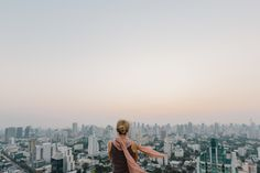 Woman looking cityscape from the roof of a tall building in Bangkok.