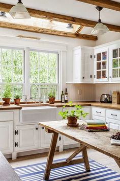 White cabinets with wood counter tops. Farmhouse sink. Big window. Wooden beams on the ceiling.