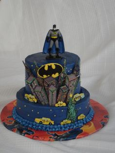 Batman - Batman cake for my little superhero's 4th birthday tomorrow. It is my take on the popular Wilton 'spiderman' cake.  I also used a cake from the whimsical bakehouse book as my inspiration.  I can tell I have been out of practice for awhile.  I had a little trouble with the buttercream this time.  I think I am starting to prefer fondant!  Only the 2nd time I have stacked a buttercream cake, boy I find fondant stacking much easier! The images are chocolate transfers and the batman is a…