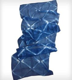 This blue scarf is handmade from silk chiffon and hand-dyed using Shibori techniques to create a unique diamond pattern.