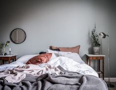 Bedroom with grey painted walls, cozy bedding and round mirror. Scandinavian decoration and ideas.
