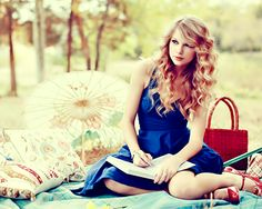 Taylor Swift.  Love this whole picture--the picnic, the parasol, her oufit, and her hair.  :)