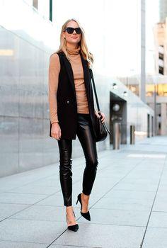 Mulher loira parada na calçada posa para foto vestindo turtleneck caramelo, colete longo preto, calça skinny preta, scarpin preto, óculos escuros e bolsa preta