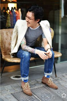 Shop this look for $150:  http://lookastic.com/men/looks/blazer-and-crew-neck-t-shirt-and-jeans-and-desert-boots-and-socks/71  — White Blazer  — White and Black Horizontal Striped Crew-neck T-shirt  — Blue Jeans  — Brown Suede Desert Boots  — Blue Socks