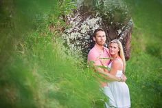 Engaged Couple hide in grass for photo