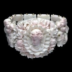 Close-up view of the bracelet from the carved conch-shell parure, Italian (Naples), c. 1860. The parure was very likely carved and mounted in Naples, the centre of the shell and coral carving industry, or from one of the importers of Neapolitan jewellery in London. This parure has been in the De Beaumont family since the 19th C. Its excellent condition suggests that it was scarcely worn. It may instead have been displayed, as a gift at a wedding or as a souvenir of a visit to Italy.
