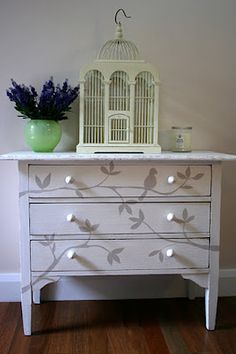 Painted dresser with tree branches and birds.